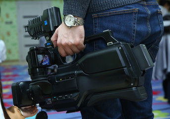 Videographer takes video camera with free copy space for text., Video camera operator working with his equipment., close up of television operator with camera . Covering an event with a video camera.