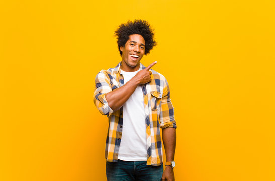 young black man smiling cheerfully, feeling happy and pointing to the side and upwards, showing object in copy space against orange wall