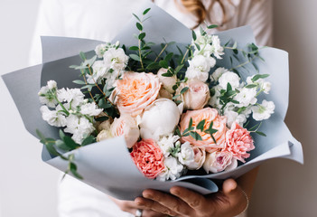 Very nice young woman holding a beautiful blossoming flower bouquet of fresh mattiolas, roses, peony, carnations, eucalyptus in pastel pink colour on the grey wall background
