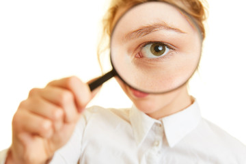 Woman looks with eye through magnifying glass to check