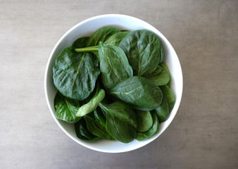 White Bowl with Fresh Baby Spinach on a Gray Background