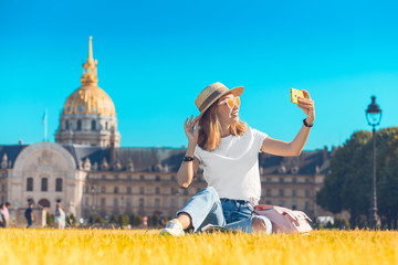 Asian happy girl traveler taking selfie pictures in the square near the Invalides In Paris. Lifestyle and tourism in France