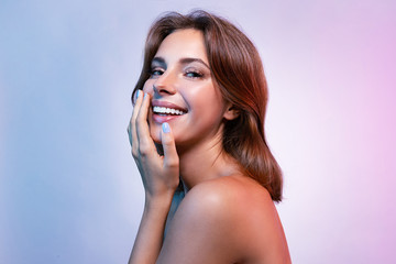 Portrait of smiling woman looking at camera with happiness. Beautiful lady touching face with hand. Wonderful model with short brunette hair posing in studio. Skincare and spa concept