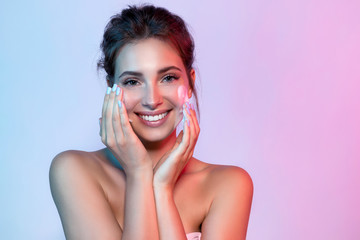 Portrait of beautiful woman applying skin cleansing foam and looking at camera with joyfulness. Wonderful young model using facial moisturizing cosmetic. Beauty and clean skin concept