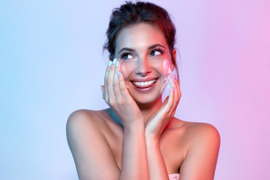 Young woman with bare shoulders using facial moisturizing cleansing. Portrait of beautiful lady looking away with happiness.Beauty and skin concept