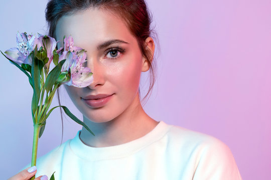 Portrait of beautiful woman closing half of face by spring flower. Beautiful lady with perfect clean skin and natural make-up looking at camera with happiness. Beauty and fashion concept