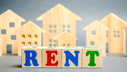 Wooden blocks with the word Rent and wooden houses. The concept of renting housing and real estate. The cost of a rented home or apartment. Rental.