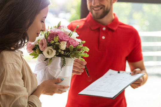 selective focus of woman smelling flowers near delivery man holding clipboard