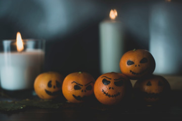 Happy Halloween citrus, tangerines painted with scary, funny faces. Dark photo with candles. Alternatives to traditional Halloween pumpkins.