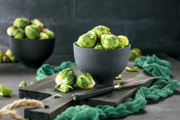 Fresh raw brussels sprouts on a dark wooden table