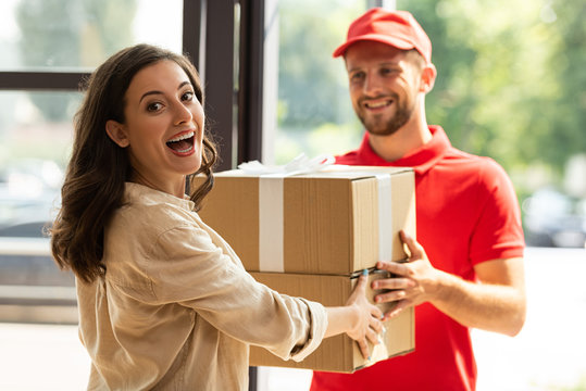 selective focus of happy woman receiving carton boxes from cheerful delivery man in cap