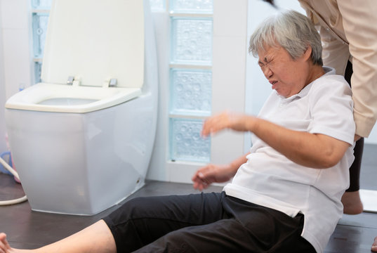 Asian elderly woman on floor in bathroom after falling down because slippery surfaces,caregiver or nurse assisting care,help,support to her,sick senior fell to the floor in toilet because of dizziness