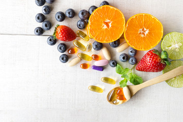 Multivitamins and supplements with fresh and healthy fruits on white wooden background.