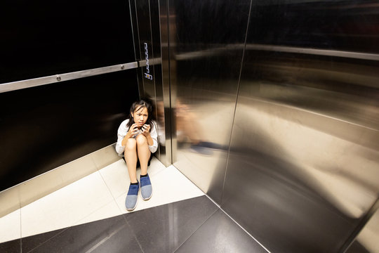Anxiety asian child girl having panic disease attack in an elevator, depressed teenage girl with mental health illness and narrow fears, suffocation, heart palpitation suffer from panic disorder