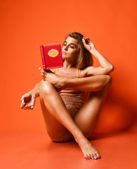 In de dag Ontspanning young fitness woman in sportswear doing yoga, stretching her leg, reading a book on studio backdrop orange background. athletic girl exercise, training, workout, stretching, relaxation