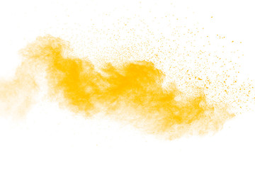 Abstract yellow powder explosion on white background.Freeze motion of yellow dust particles splash.