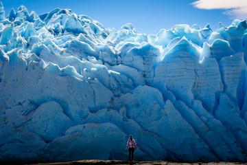 A female tourist is standing in front of Perito Moreno Glacier, Los Glaciares National Park in Santa Cruz Province, Argentina