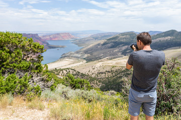 Man taking picture of Sheep Creek Overlook in Manila, Utah near Flaming Gorge National Park with cloudy valley and river