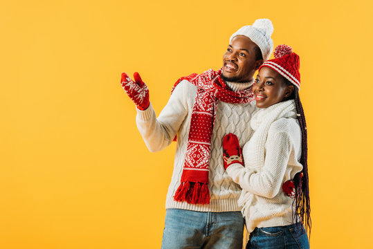 African American man in winter outfit hugging woman and pointing with hand isolated on yellow