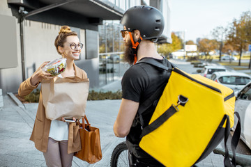 Male courier delivering food on a bicycle, giving bag with fresh takeaway lunch to a young business...