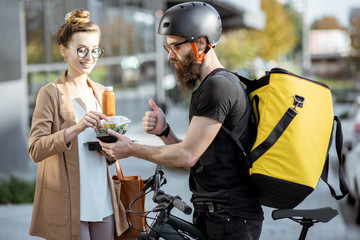 Courier delivering fresh lunches to a young business woman on a bicycle with thermal backpack. Takeaway restaurant food delivery concept