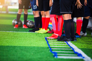Selective focus to soccer player team are standing to training. Ladder drills exercises for soccer team. Young player exercises on ladder drills. Soccer academy.