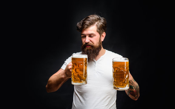 Celebration oktoberfest festival. Beard man drinking beer from mug. Young man tasting draft beer. Lager and dark ale. Beer time. Bearded man holds beer glass. Handsome man drinks ale at bar or pub.