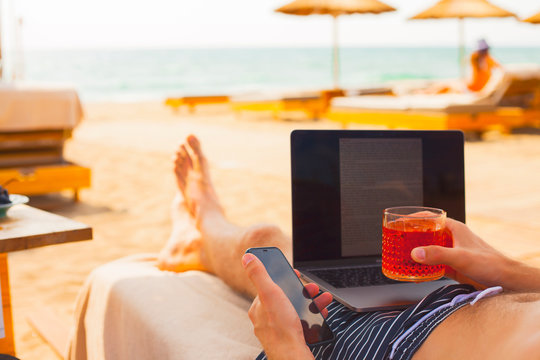 Young business man with cocktail working on laptop on the beach in sunny day, freelance job online. Vacation, lifestyle and work concept.