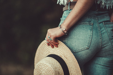 Fotobehang Boho Stijl Stylish fashion woman in jeans shorts with silver turquoise rings holds a straw hat. Boho chic fashion and denim style
