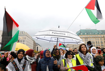 People wave Palestinian flags as they gather in front of the  Brandenburg Gate in Berlin