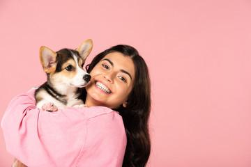 beautiful smiling girl holding Welsh Corgi puppy, isolated on pink