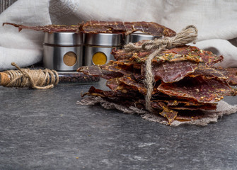 Dried meat slices with spices in jars, copy space