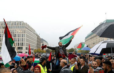 People react and wave Palestinian flags as they wait for a performance of Palestinian rappers Shadi Al-Bourini und Shadi Al-Najjar, in front of the Brandenburg Gate in Berlin