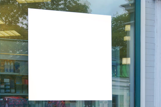 advertising blank white sign on glass of window showcase shop outside on city street, mock-up
