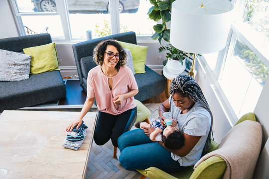 High angle view of cheerful lesbian looking at girlfriend feeding milk to baby boy in living room at home