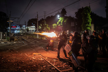 Riot police officers fire tear gas during a students' protest near the Indonesian parliament building in Jakarta