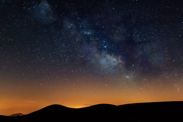 Photograph of the night sky in the mountains, with a view of the Milky Way. Visible stars during sunset. Galaxy, universe. Wall mural