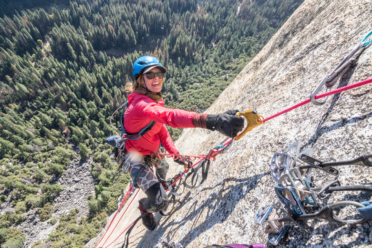 A young woman is all smiles while jumaring on a fixed rope way high up