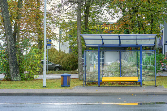 empty glass bus stop with yellow bench near road in city