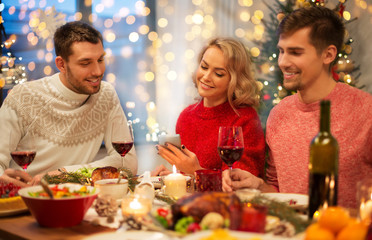 holidays and celebration concept - happy friends with smartphone having christmas dinner at home