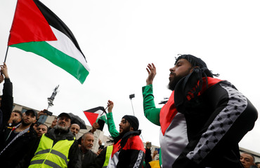 People react and wave Palestinian flags as they gather in front of the Brandenburg Gate in Berlin