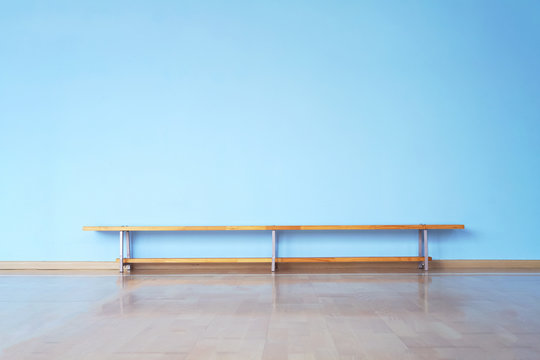 wide laminate floor and huge empty blue wall in empty room with wooden bench