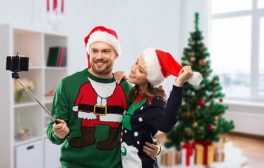 celebration, technology and winter holidays concept - happy couple in santa hats taking picture by smartphone on selfie stick at ugly sweater party over christmas tree at home background