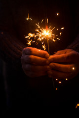 Christmas and new year eve concept image with close up of a pair of man hands taking a red fire sparkler to celebrate the night party - focus on fireworks and hope for people future