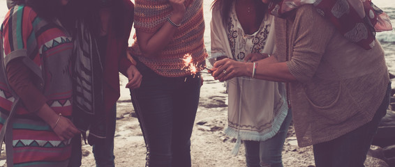 trendy boho fashion style and friendship celebration group of happy unrecognizable people with sparklers fire in outdoor leisure activity together -  love and friends alternative lifestyle
