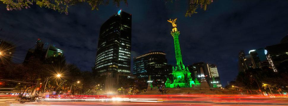 Panoramica de larga exposicion en el  Angel de la Independencia de la Ciudad de Mexico, de noche y con edificios de fondo.