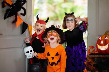 Kids trick or treat. Halloween. Child at door.