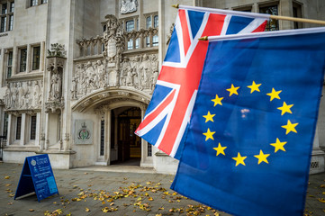 EU and UK flags hanging at the Supreme Court of the United Kingdom, which focuses on cases that are of importance to the general public, like the Brexit ruling, in London, UK