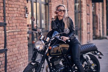 Stylish mature female is posing on photographer on her new shiny retro bike. Wall mural