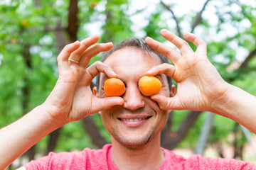 Man holding apricots with trees in orchard in background Fruita Capitol Reef National Monument in summer covering eyes and smiling